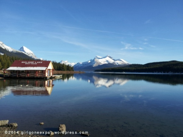 Curly boat house on maligne lake with snowcapped mountains